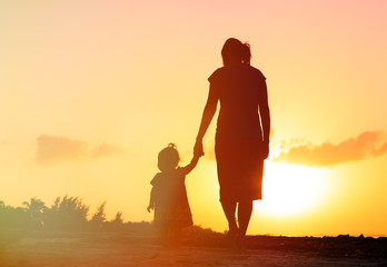 mother and little daughter walking at sunset