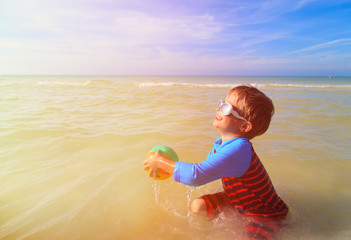 little boy playing ball on summer beach