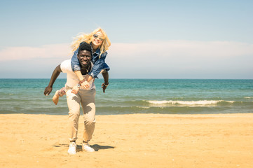 Young multiracial couple at the beach having fun with piggyback