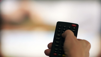 Woman changes the channels on the TV