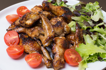 Close up of chicken wings fried with honey decorated tomatoes an