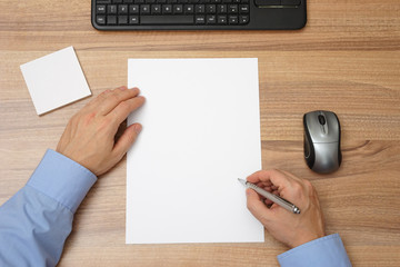 Businessman  with blank paper and pen in hand  to begin with wri