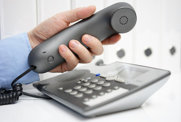adviser is picking up telephone handset, support concept