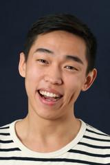 Laughing young Asian man looking at camera