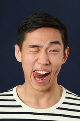 Funny young Asian man making face and showing his tongue