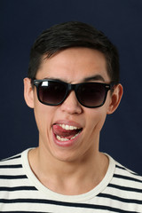 Funny young Asian man in sunglasses showing his tongue
