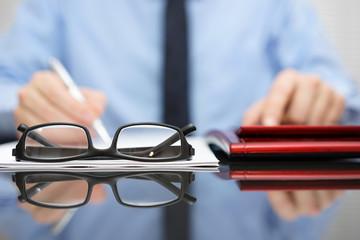 blurred businessman is working in office , focus is on eyeglasse