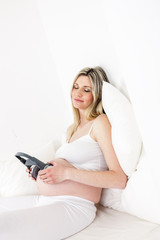 pregnant woman with headphones resting in bed