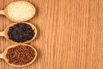 Red, white, and black rice in a wooden spoon on a wooden table