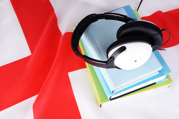 Books and headphones on England flag background