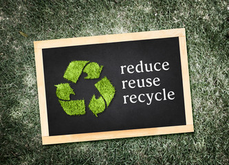 "Top view of recycle symbol and ""reduce reuse recycle"" word on bl"