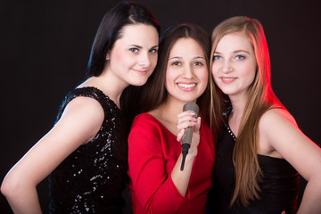 Three beautiful girls with microphone