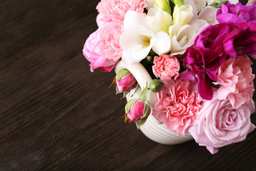 Beautiful spring flowers in pot on wooden background