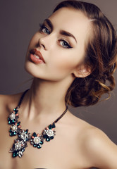 beautiful girl with dark hair and luxurious necklace