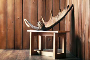 Moose antler on stool on wooden background