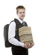 The schoolboy in a school uniform with a huge pack of books..