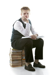 schoolboy inschool uniform sits on pack of books with book