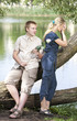 Young guy and girl on nature near lake after quarrel..