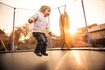 Child jumping trampoline at sunset