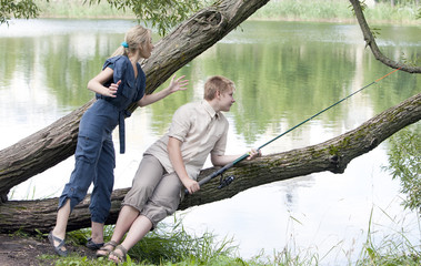 The young guy with a rod and the girl shows the size of fish