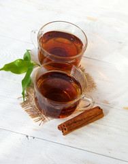 Glass cup of tea with cinnamon sticks