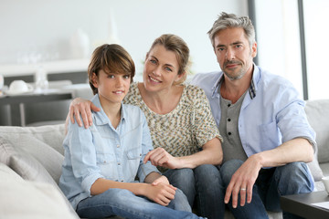 Portrait of happy family of three sitting in sofa at home