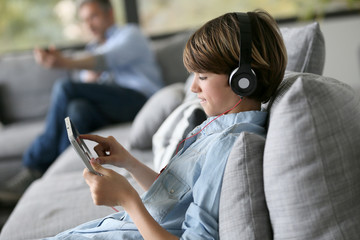 Tenager watching movie on digital tablet with headphones on