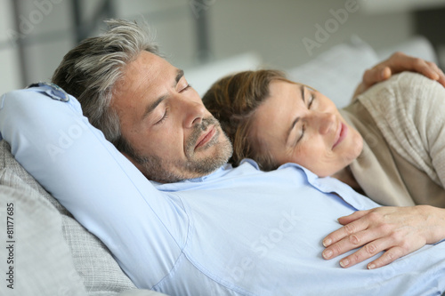 Mature couple having a rest laying down in sofa - 81177685