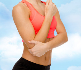 sporty woman with pain in elbow