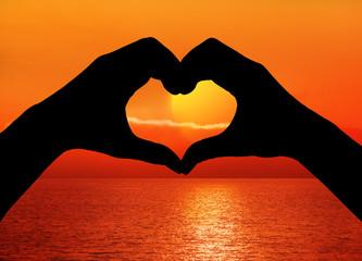 Hand mit Herz vor Sonnenuntergang