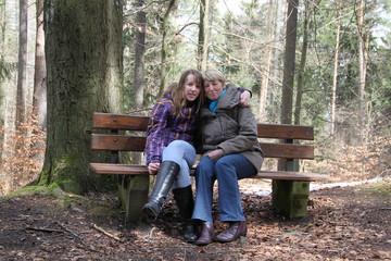 Mädchen mit Oma pausieren bei Wanderung im Wald