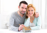 Young attractive 30s couple making home project poster