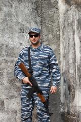 Caucasian manin urban warfare holding rifle