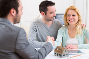 Young happy couple handshaking real estate agent after signing c