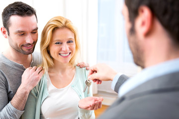 Real estate agent delivers keys of new house to young couple