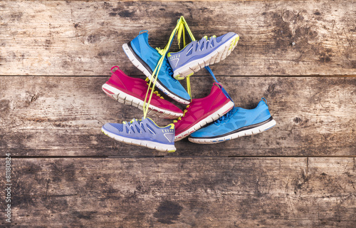 Sports shoes hang on a nail on a wooden fence background - 81180824