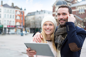 People on holidays visiting city helped by tablet