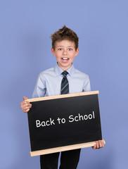 Back to School. Boy with Blackboard Slate on Blue Background.