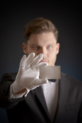 butler wearing white gloves and holding a business card
