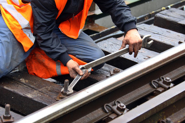 Worker tightens the screw on railroad with two spanners in hands