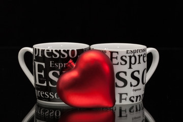 Two empty coffee cups and red heart