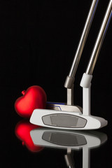 Two different golf putters and red heart
