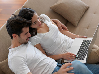 relaxed young couple working on laptop computer at home