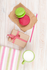 Colorful macarons, cup of milk and gift box