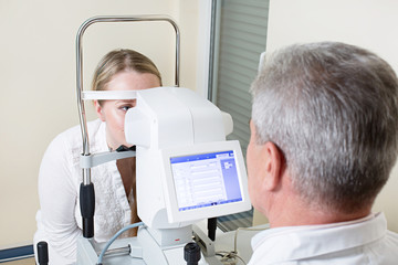 Young woman having her eyes examined by an eye handsome elderly