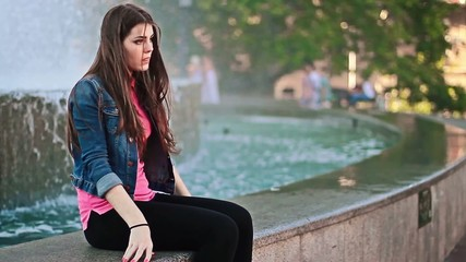 A girl sits at the fountain