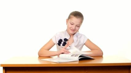 Smiling, little school girl reading the book, doing her homework