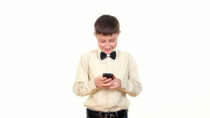 School boy sending message using mobile phone and smiles on