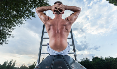 Back view of a man exercising on bench