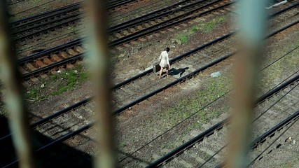 Offended woman with old suitcase walking along railroad